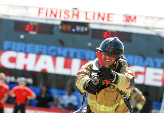 "Rob Demski, of the St. Lucie County Hooligans, drags a hose in a team relay against Polk County Fire Rescue during the 3M Scott Firefighter Combat Challenge US Nationals on Saturday, Oct. 5, 2019, at the Manatee Observation and Education Center in Fort Pierce. Competitors from more than 45 cities and other countries compete wearing full bunker gear in a linked series of five tasks including climbing a 5-story tower, hoisting, chopping, dragging hoses and rescuing a 175 lb. ""victim"". ""This is a physical fitness competitive sport for firefighters which gives them a purpose in what they do,"" said Todd Shelton, operations manager of the 3M Scott Firefighter Combat Challenge."