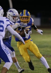 Nordhoff High's Kaden Monson looks for an opening downfield while being surrounded by two Fillmore players during Friday night's Citrus Coast League game in Ojai. Nordhoff won, 35-6.