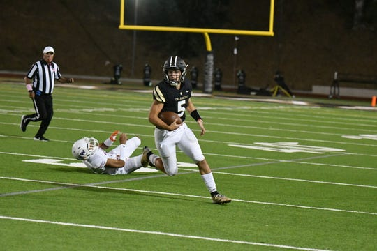 Calabasas High quarterback Jaden Casey gets away from a Westlake defender and runs downfield during the Coyotes' 54-35 victory in a Marmonte League game Friday night.