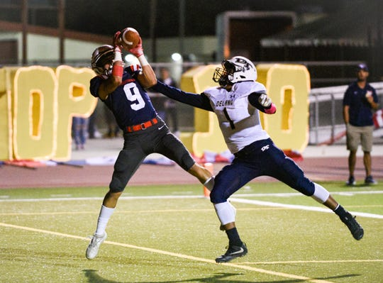 Tulare Western's Nathan Marroquin makes a valiant effort to haul in a pass against Delano in an East Yosemite League football game on Friday, Oct. 4, 2019.