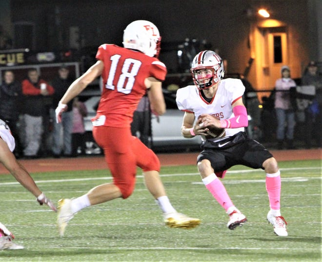 Somers quarterback Jackson Kossow stutter steps to try to elude Fox Lane's Harrison Hewitt.
