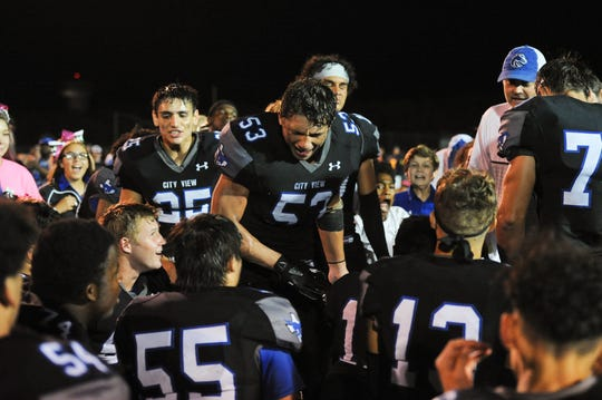 City View players including Jonathan Nabors (25, left standing) and Cade Farrell (right standing) yell and cheer in the huddle following the game.
