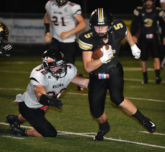 Henrietta runningback Carson Cody (5) cuts up the middle away from Nocona linebacker Chandler Fenoglio (32) during second quarter action Friday night in Henrietta.