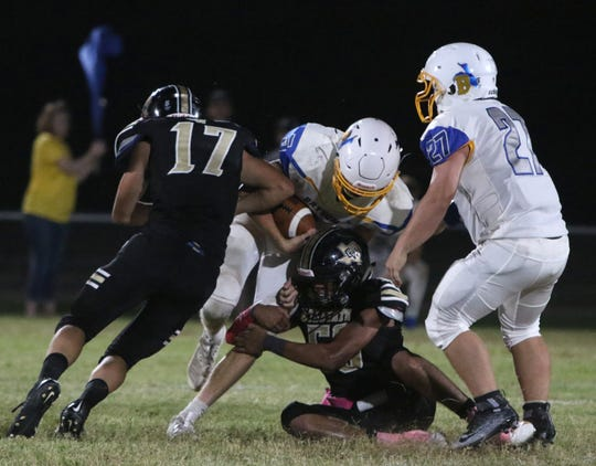 Bryson's Landon Stevens is tackled by Crowell's Dakota Degan (17) and Gabriel Gomez Friday, Oct. 5, 2019, in Crowell.The Cowboys defeated the Wildcats 54-48.
