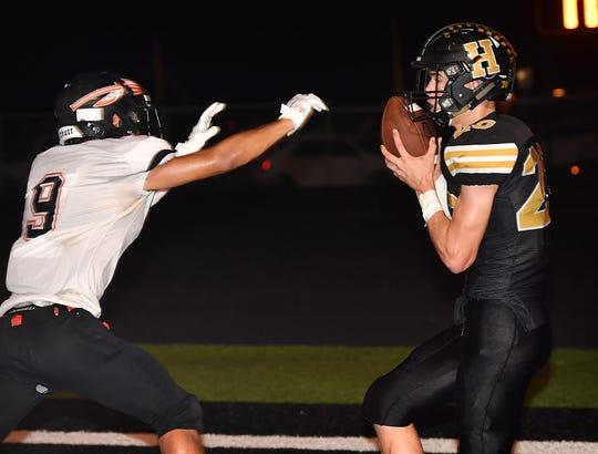Henrietta receiver Reece Essler (20) catches a touchdown pass behind Nocona's Juan Rico (9) Friday night in Henrietta.