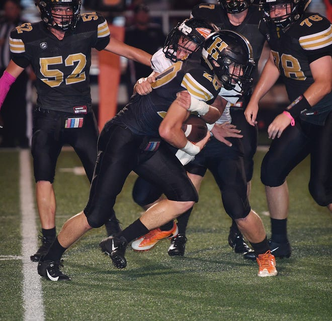 Reece Essler (20) of Henrietta carries the ball after scooping up a fumble against Nocona Friday night in Henrietta.