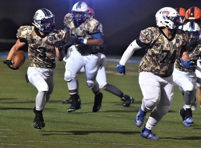 Zanesville's Jordan Martin makes his way down the side line with Parker Moorehead (74) blocking during Zanesville's 38-30 win over Mount Vernon on Friday.