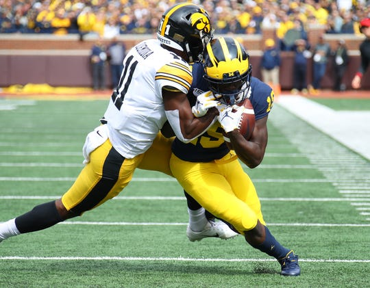 Michigan's Mike Sainristil fights for yardage while being tackled by Iowa's Michael Ojemudia during the first half at Michigan Stadium.