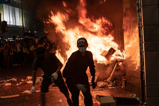 Pro-democracy protesters set a fire at the entrance of the MTR station during a demonstration in the Causeway Bay district in Hong Kong on October 4, 2019. Hong Kong's government invoked emergency powers on Friday to introduce an anti-mask law which bans people from wearing masks at public assemblies as the city remains on edge with the anti-government movement entering its fourth month.
