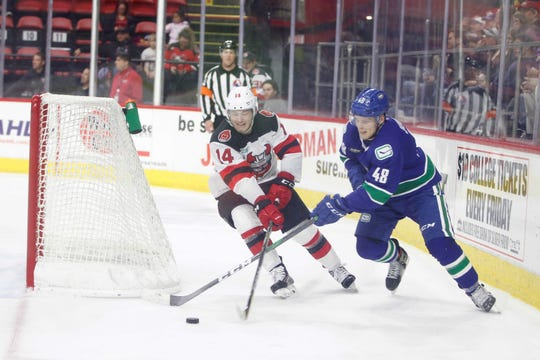 Binghamton Devils forward Joey Anderson fights for the puck with Utica's Olli Juolevi at Floyd L. Maines Veterans Memorial Arena Saturday, October 5, 2019.