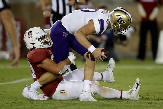 Washington quarterback Jacob Eason is sacked by Stanford's Scooter Harrington in the first half of the Husky loss. After scoring on the opening drive Washington struggled to find any momentum on offense in the 23-13 loss.