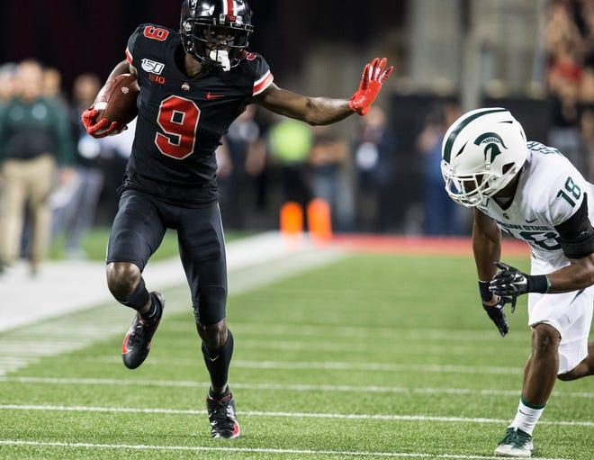 Ohio State receiver Binjimen Victor throws a stiff arm en route to scoring on a 60-yard touchdown catch in Saturday's 34-10 win over Michigan State.