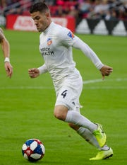 FC Cincinnati defender Greg Garza (4) dribbles away from D.C. United defender Frederic Brillant (13) in the second half of the MLS match between FC Cincinnati and D.C. United on Sunday, Oct. 6, 2019, in Washington D.C. at Audi Field.