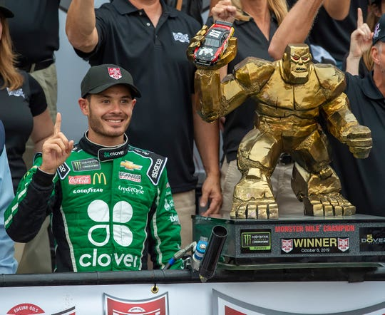 Kyle Larson stands next to the trophy after winning the NASCAR Cup Series auto race Sunday at Dover International Speedway.