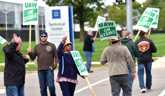 UAW GM and Aramark Local 160 active members and one retiree wave at beeping motorists as they picket in front of Gate 11 at the GM Tech Center in Warren, Saturday, October 5, 2019.
