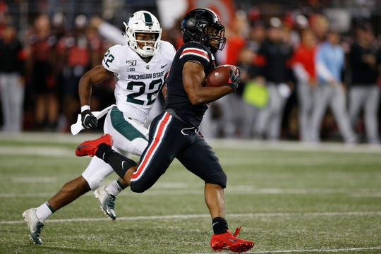 Ohio State running back J.K. Dobbins, right, heads for a touchdown while trailed by Michigan State defensive back Josiah Scott.