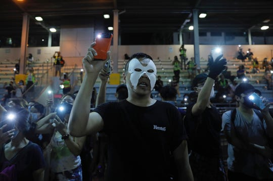 Masked protesters hold up their lit mobile phones as they sing a protest anthem in Hong Kong on Saturday, Oct. 5, 2019.