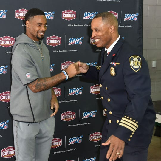 Darius Slay greets a Detroit firefighter during an appearance Friday at the Southwest Public Safety Center in Detroit.