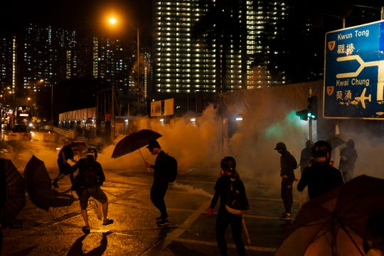Protestors face police tear gas in Hong Kong, Sunday, Oct. 6, 2019.