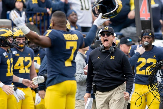 Michigan head coach Jim Harbaugh celebrates with linebacker Khaleke Hudson after Hudson helped keep Iowa from converting a fourth down late in the fourth quarter.