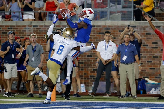 SMU wide receiver James Proche catches the winning touchdown pass while Tulsa safety Brandon Johnson defends during the third overtime.