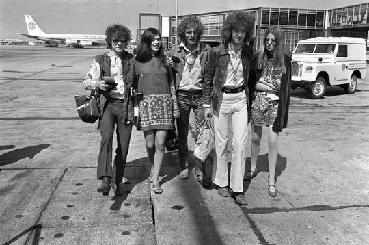 In this Aug. 20, 1967 file photo, members of the rock group Cream depart from Heathrow Airport in London,  for their American tour. The trio, walking with unidentified female companions, from left are, base guitarist Jack Bruce, drummer Ginger Baker, and lead guitarist Eric Clapton.
