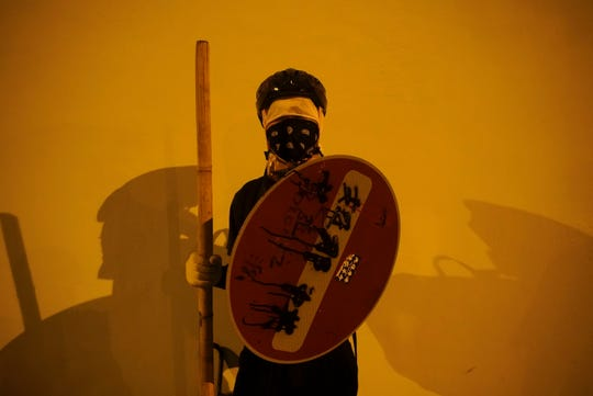 A masked protester holding a shield.