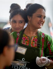 Sadaf Jawad, right, serves food while her daughter Rida Jawad rests her head on her mother's shoulder at the Islamic Society of Evansville's 18th Annual International Food Festival in Newburgh, Sunday afternoon.