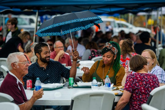 Jake Stahl of Evansville, center left, holds an umbrella for Kana Brown of Evansville as they enjoy lunch at the Islamic Society of Evansville's 18th Annual International Food Festival in Newburgh, Sunday afternoon.