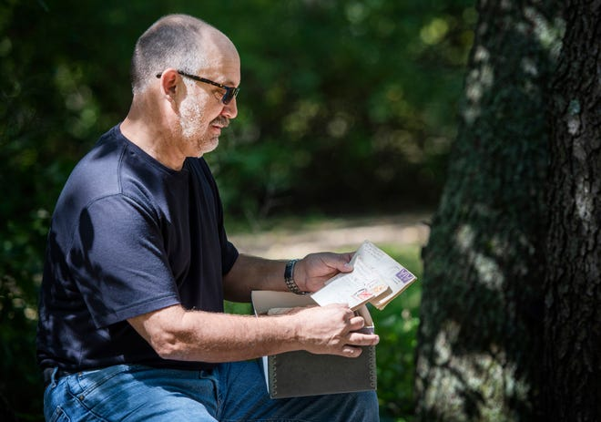 Dave Sheen holds notes written by his father during World War II on Tuesday, Sept. 17, 2019, at his home in Janesville, Wis. Sheen and a friend traveled to Europe in July to retrace the footsteps of Sheen's father, Merle, during the war.