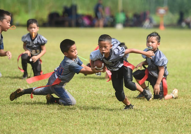 Guam Raiders player Ian John Blas, right, attempts to avoid the Island Broncos' Noah Quichocho during their GYNFF game at the Mikkel Tan I. Vy Field in Tiyan, Oct. 6, 2019.