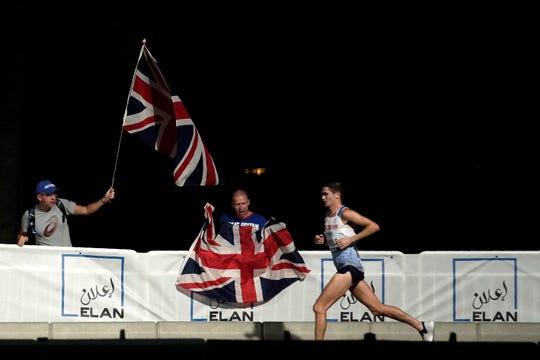 People cheer Callum Hawkins, of Great Britain, during the men's marathon at the World Athletics Championships in Doha, Qatar, Sunday, Oct. 6, 2019.