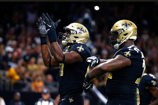 New Orleans Saints tight end Jared Cook celebrates his touchdown reception with offensive tackle Terron Armstead (72) in the first half of an NFL football game against the Tampa Bay Buccaneers in New Orleans, Sunday, Oct. 6, 2019. (AP Photo/Butch Dill)