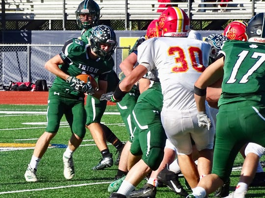 Fisher Catholic's Alex Smith takes a handoff from quarterback Kaden Starcher during the Irish's 31-21 loss against Worthington Christian on Saturday at Fulton Field.
