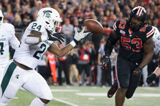 Oct 5, 2019; Columbus, OH, USA; Michigan State Spartans running back Elijah Collins (24) loses control of a pitchout as Ohio State Buckeyes defensive tackle Davon Hamilton (53) closes in at Ohio Stadium. Mandatory Credit: Greg Bartram-USA TODAY Sports