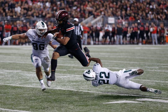 Ohio State quarterback Justin Fields, center, is tackled by Michigan State defensive lineman Jacub Panasiuk, left, and defensive back Josiah Scott during the second half of an NCAA college football game Saturday, Oct. 5, 2019, in Columbus, Ohio. Ohio State won 34-10. (AP Photo/Jay LaPrete)