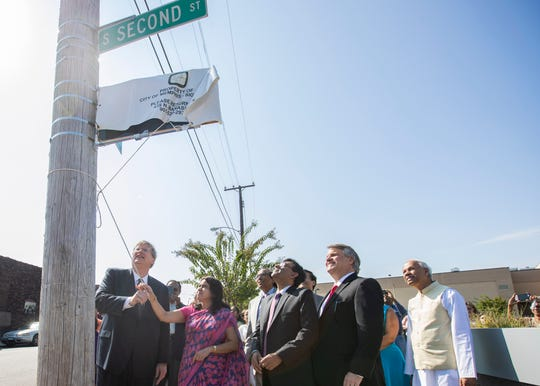 """Mayor Jim Strickland and Dr. Swati Kulkarni, consul general of India in Atlanta,  unveil an honorary street sign named """"Gandhi Way"""" by the National Civil Rights Museum on Saturday, Oct. 5, 2019."""