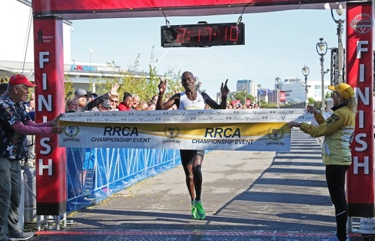 The first-place men's finisher Sammy Rotich crosses the finish line at the 2019 Milwaukee Lakefront Marathon.