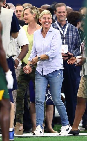 Ellen DeGeneres walks on the sidelines before the Packers-Cowboys game Sunday with her spouse Portia de Rossi (left).