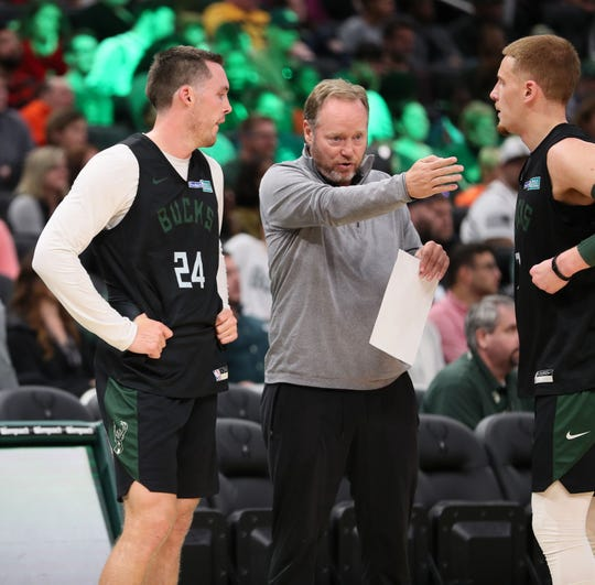 Pat Connaughton, left, and Donte DiVincenzo, right, get instructions from coach Mike Budenholzer.