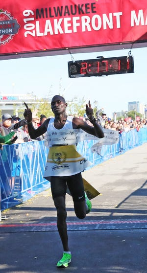The top men's finisher Sammy Rotich crosses the finish line at the 2019 Milwaukee Lakefront Marathon.