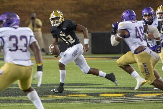 ASU quarterback Kha'Darris Davis (12) looks for a receiver as Alcorn State players close in on him.