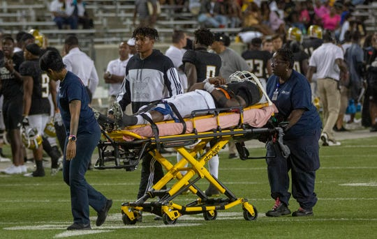 ASU quarterback Kha'Darris Davis (12) is wheeled off the field after he suffers an injury late in the fourth quarter.