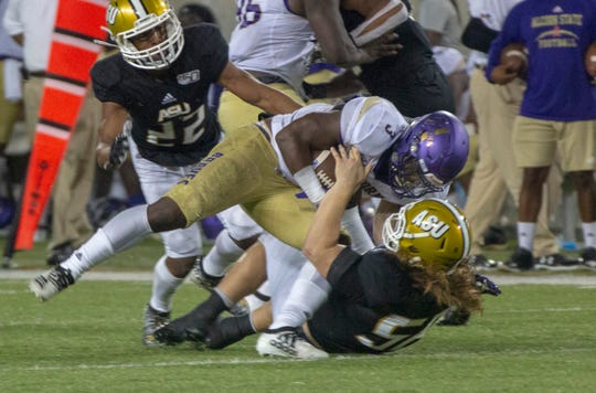 ASU linebacker Colton Adams (56) pulls Alcorn running back De'Shawn Waller (3) to the ground for a tackle during the third quarter.
