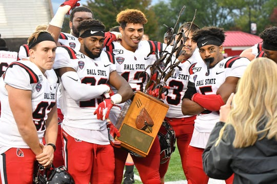 Ball State players celebrate with the Bronze Stalk Trophy after the Cardinals' win against Northern Illinois.