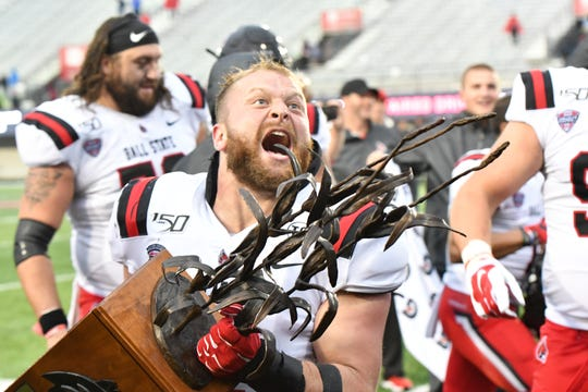 Ball State linebacker Jacob White celebrates with the Bronze Stalk Trophy after the Cardinals' win against Northern Illinois.