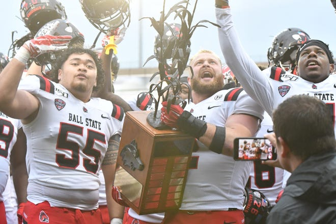 Ball State players celebrate with the Bronze Stalk Trophy after defeating Northern Illinois.