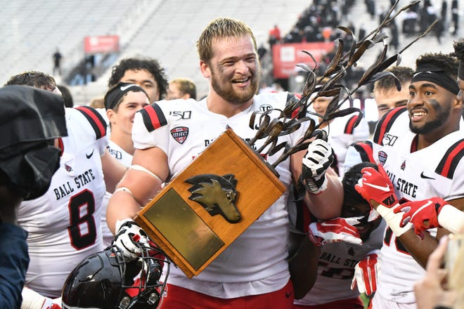Ball State offensive lineman Danny Pinter holds the Bronze Stalk Trophy after the Cardinals' win against Northern Illinois.