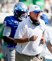 MTSU head coach Rick Stockstill runs off the field after checking on an MTSU safety Gregory Grate Jr. (3) who wa injured on a play during the game against Marshall on Saturday Oct. 5, 2019, at MTSU.