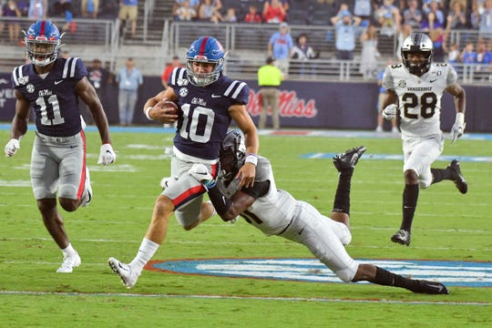 Mississippi Rebels quarterback John Rhys Plumlee (10) runs the ball while defended by Vanderbilt Commodores defensive back Cam Watkins (31) during the first quarter at Vaught-Hemingway Stadium.